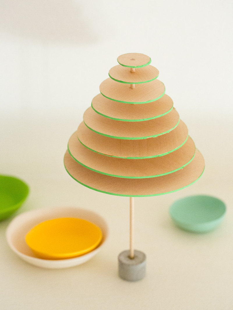 A close up of DIY modern mini balsa wood Christmas tree with small bowls below.