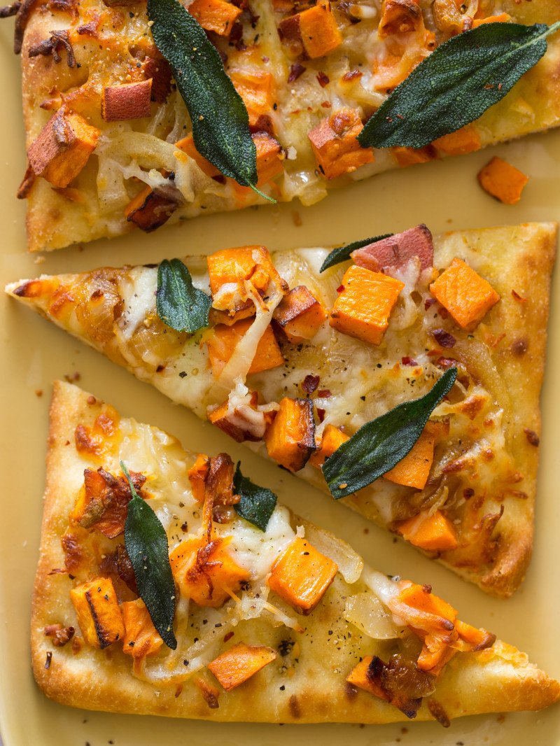 A close up of slices of sweet potato and caramelized onion flatbread.