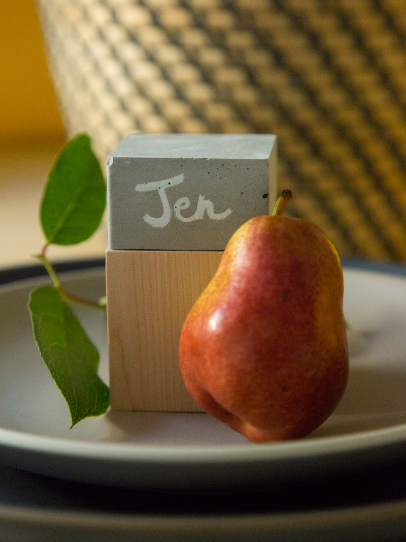 A close up of a DIY cement and wood place card with a pear.