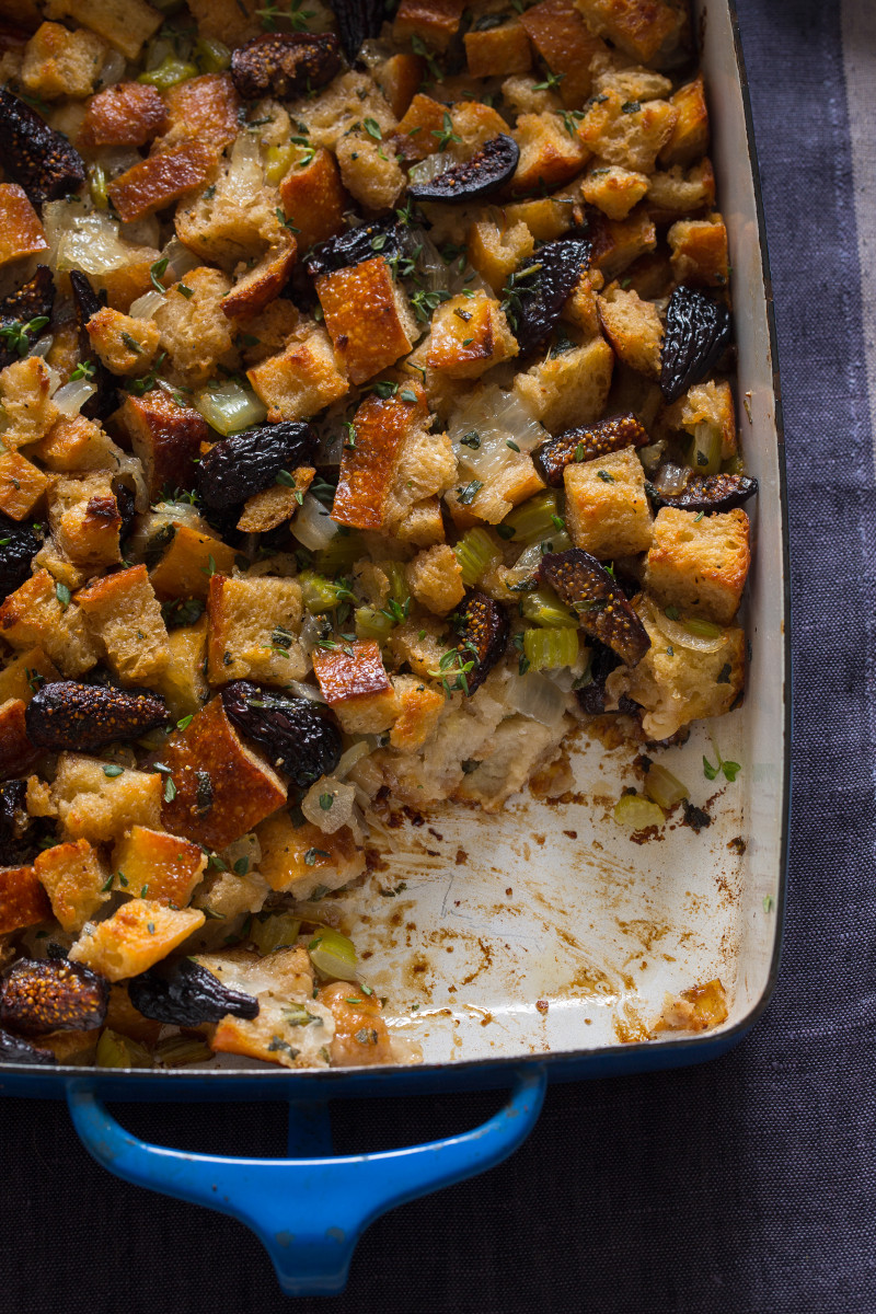 A close up of fig, herb, and sausage stuffing with a portion taken out.