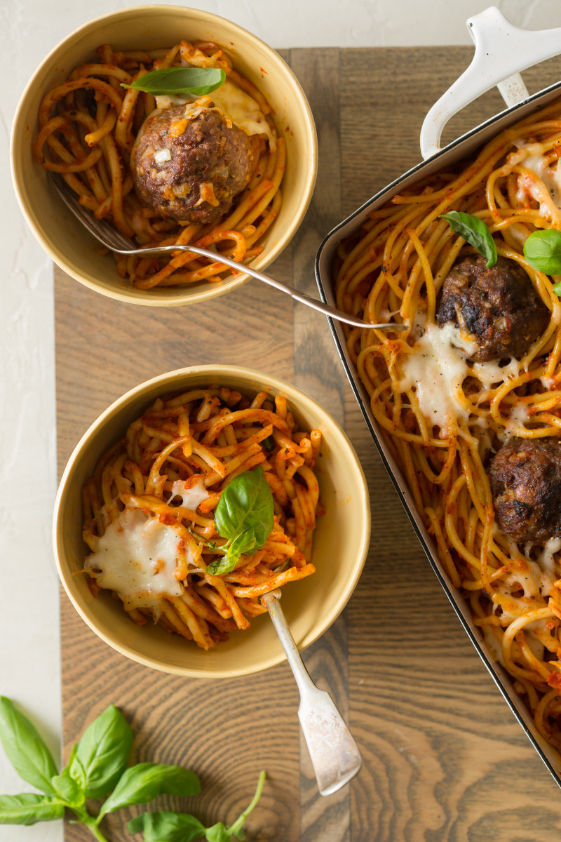 Baked bucatini and meatballs in a baking dish next to bowls served with forks.