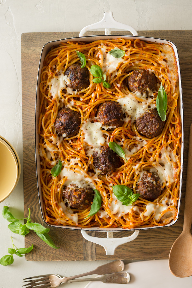Baked bucatini and meatballs in a baking dish on a wood cutting board.