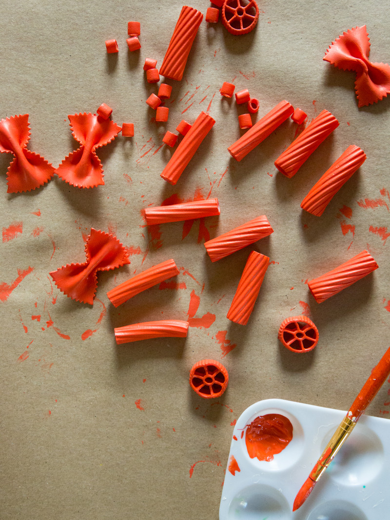 Different types of dry pasta noodles painted red to use for DIY pasta gift wrap.