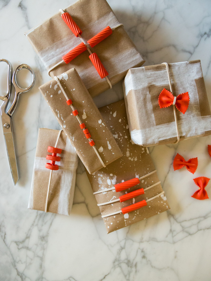 A variety of boxes wrapped in DIY pasta gift wrap with scissors.