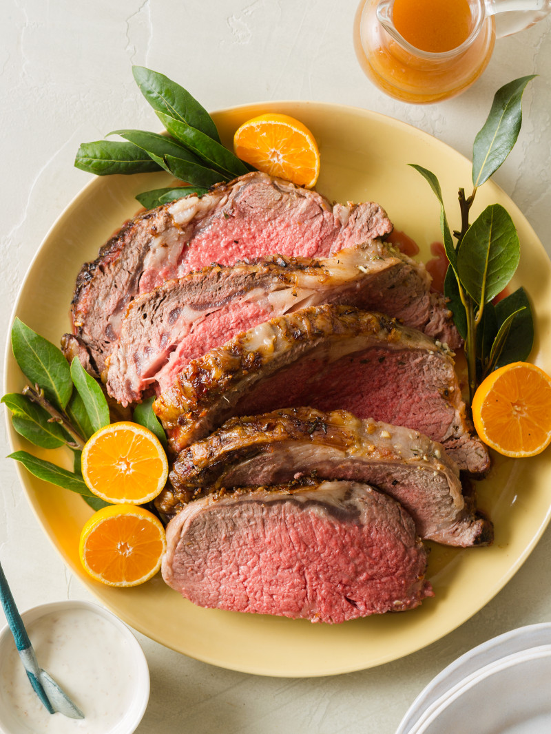 A plate of sliced standing rib roast garnished with orange halves.