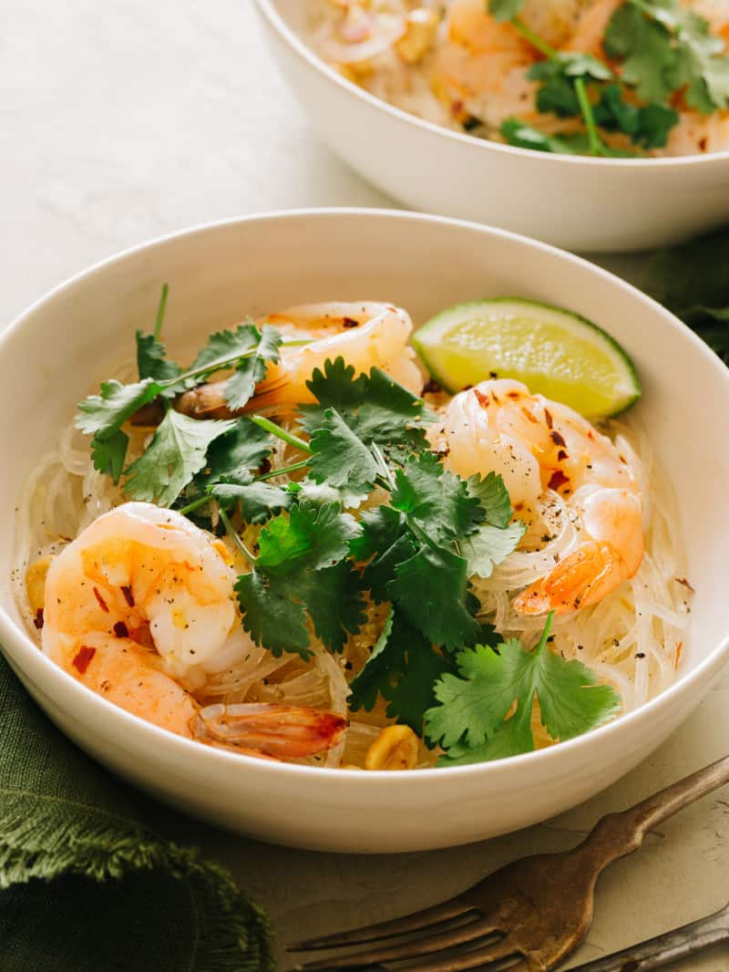 A bowl of yum wood sen with shrimp garnished with cilantro and a lime wedge.