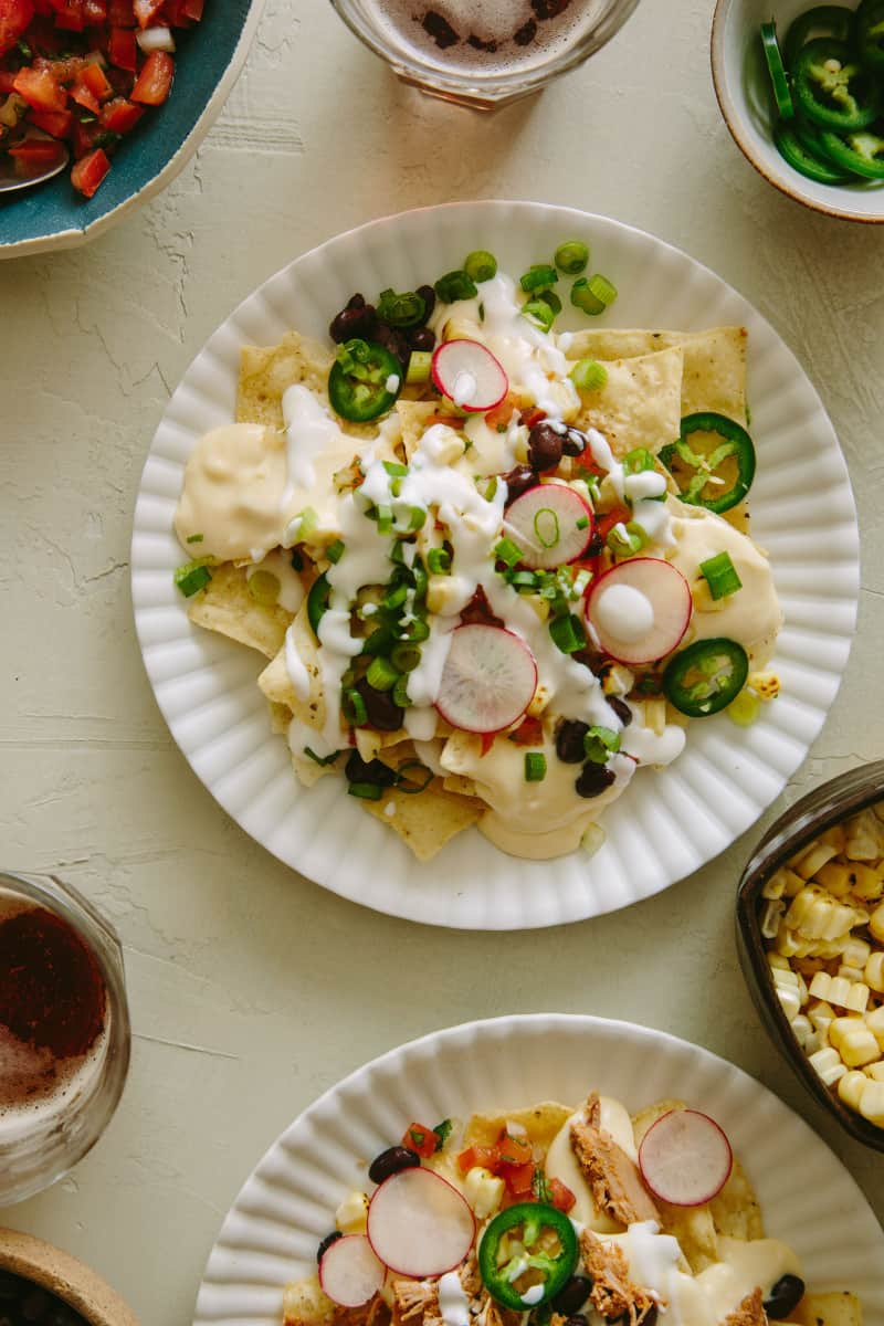 A plate of nachos made from DIY nacho bar with queso sauce.
