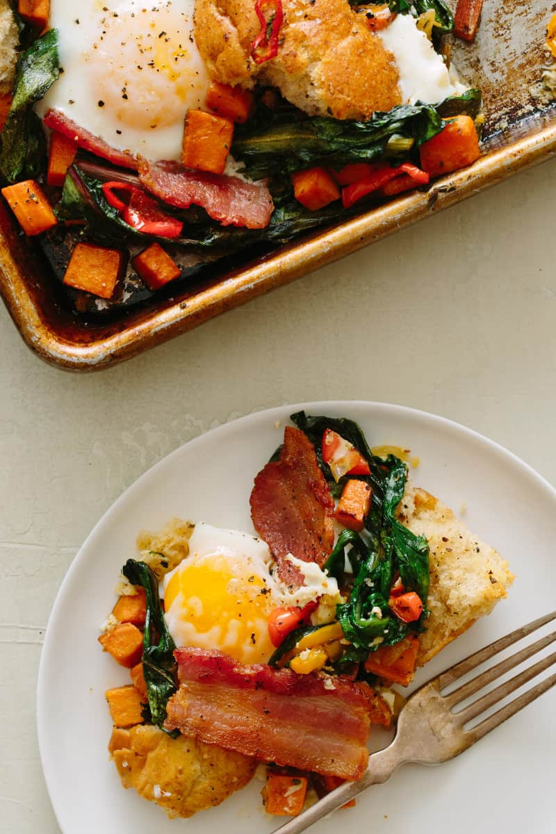 A savory breakfast pan next to a plate with a serving and a fork.