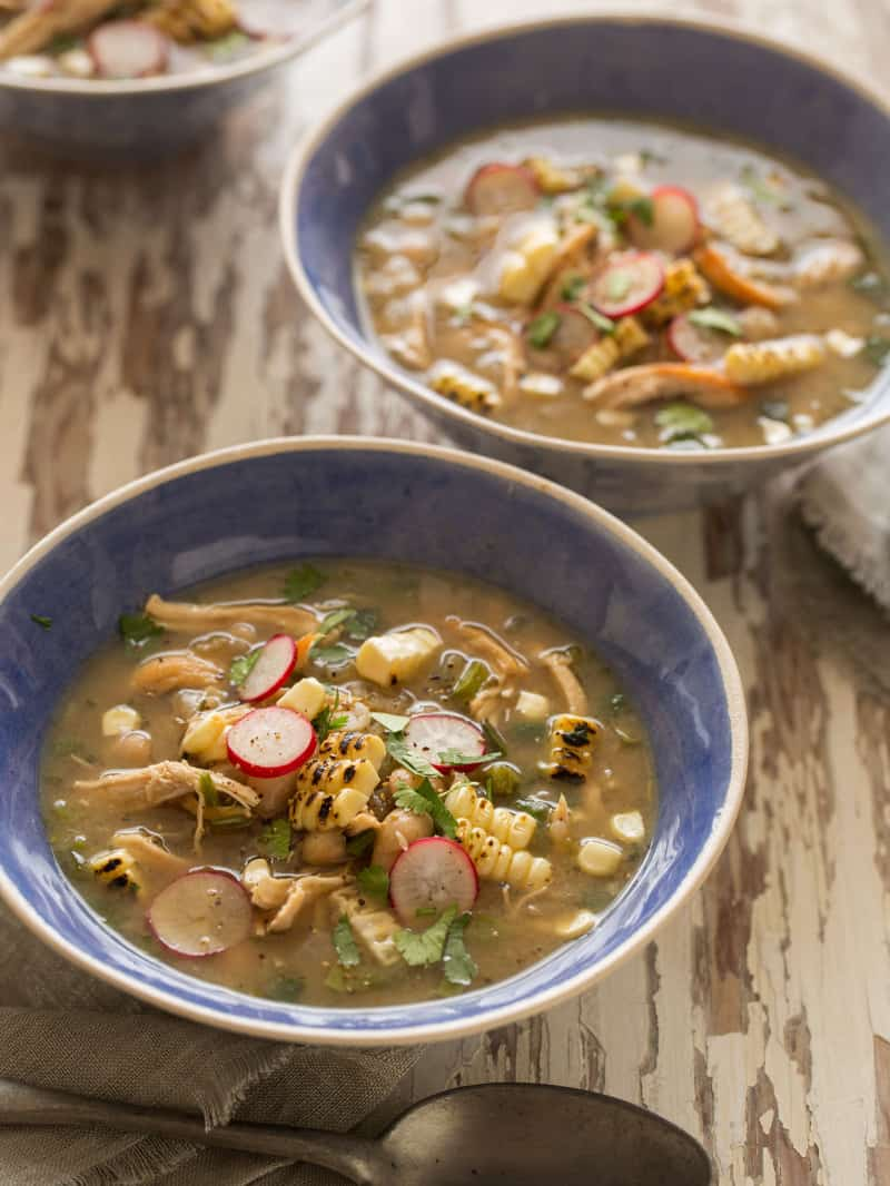 Spicy white bean chili with shredded chicken in blue bowls on a wooden table top.