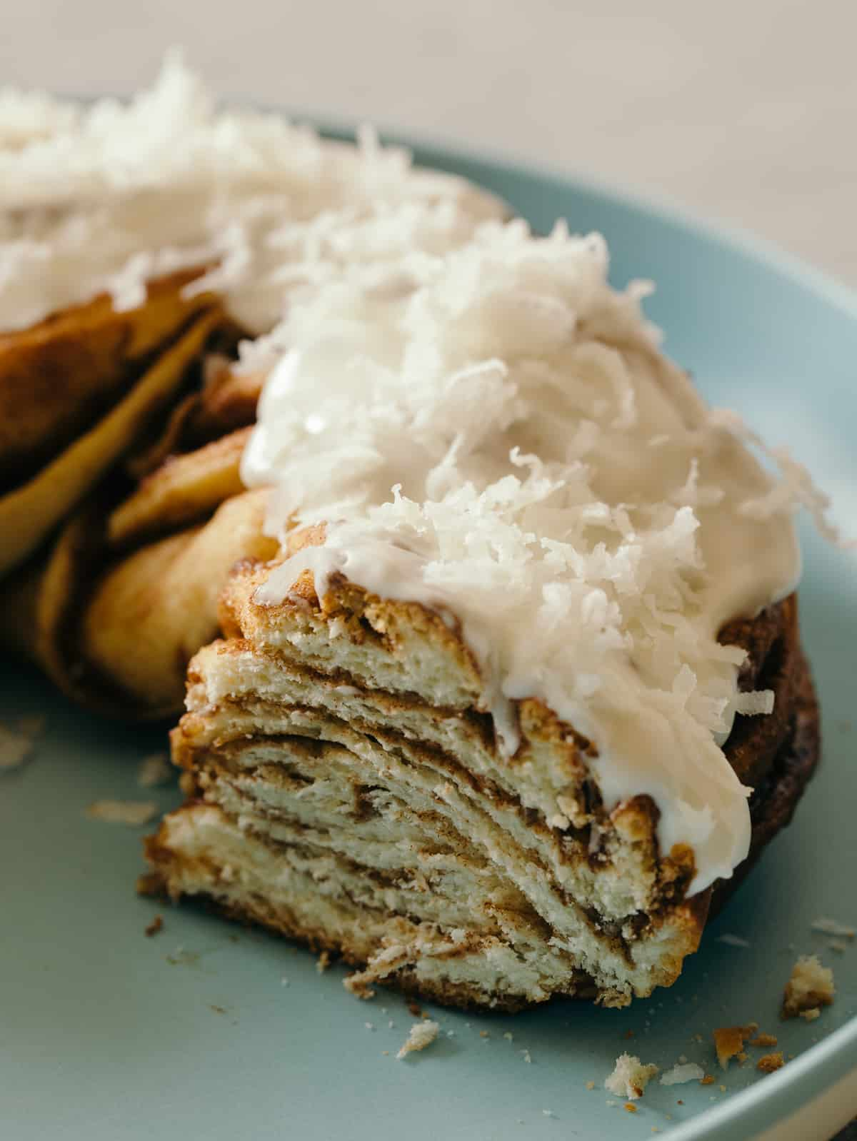 A close up of sliced brown butter braided cinnamon roll cake topped with shredded coconut.