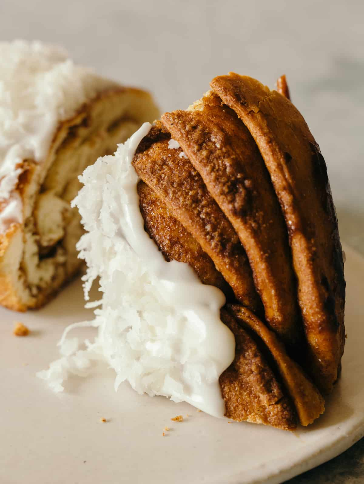 A close up of a slice brown butter braided cinnamon roll cake topped with shredded coconut.