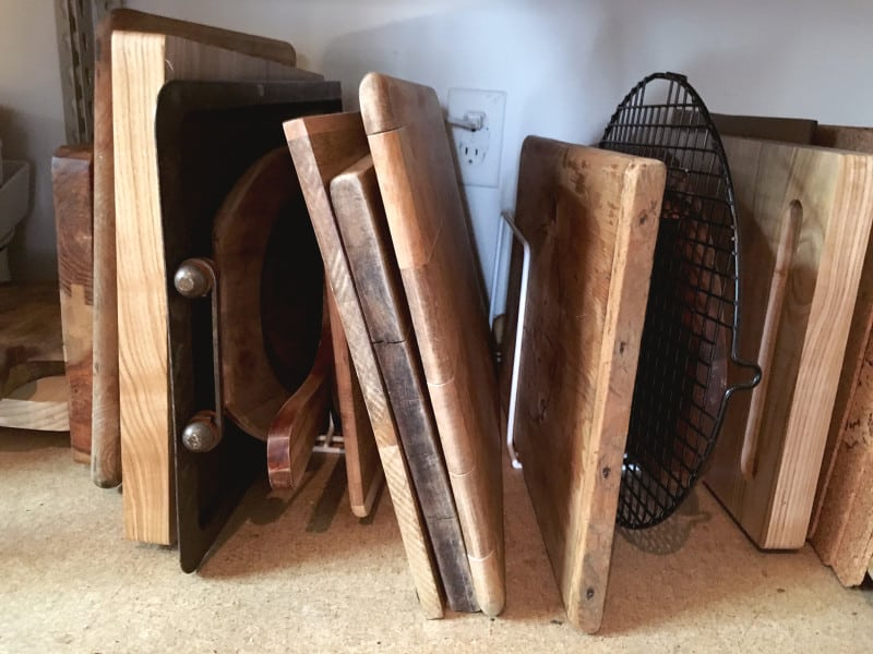 A close up of a variety of wooden cutting boards standing up in racks.