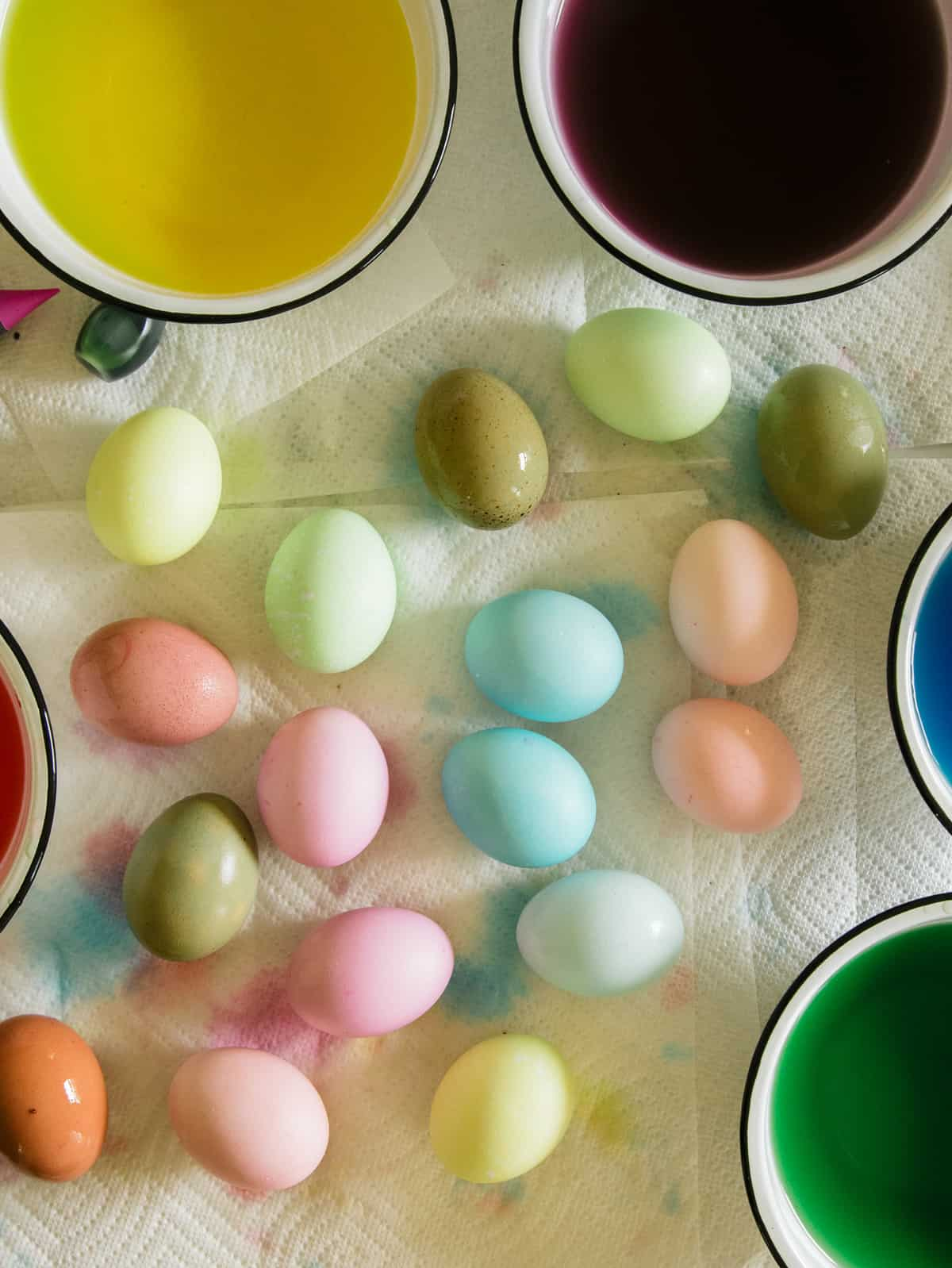 Dyed Easter eggs in a variety of colors on paper towels next to bowls of dye.