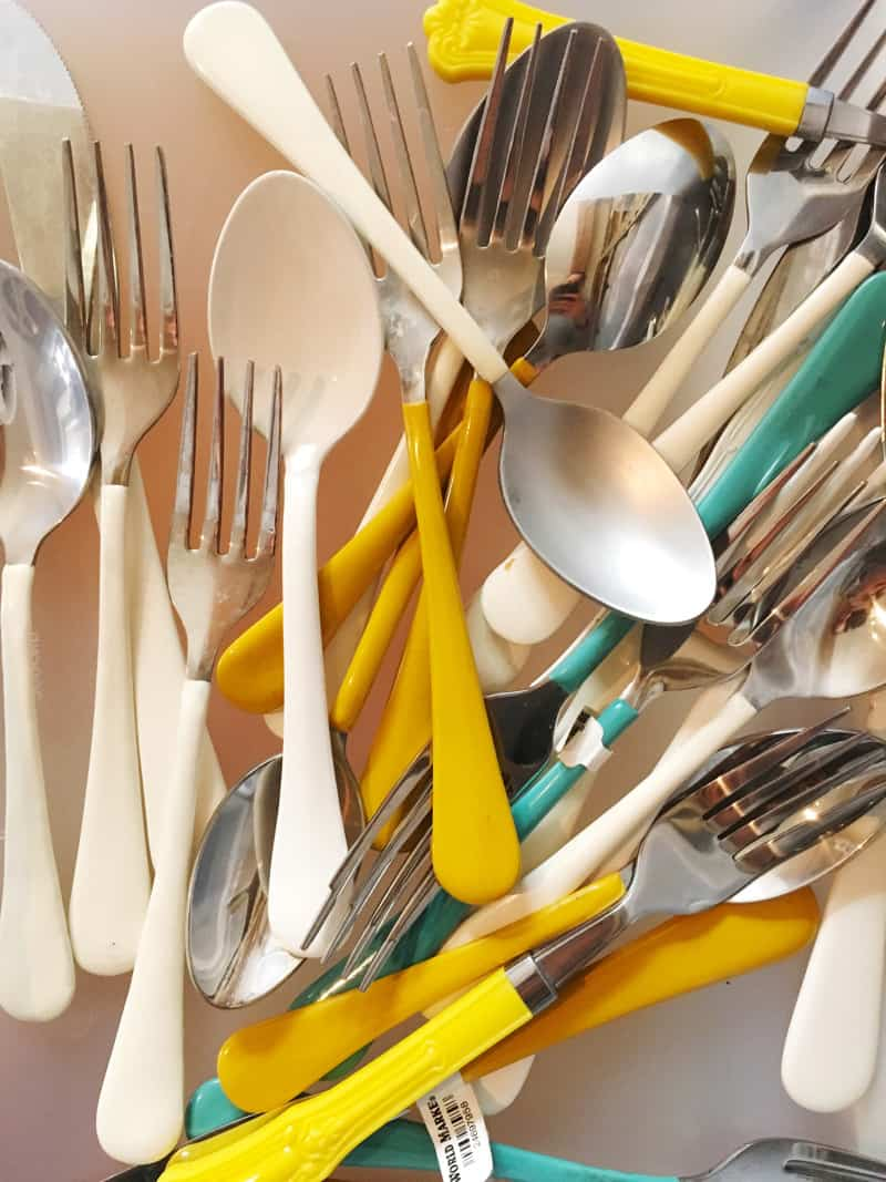 A close up of white, yellow, and teal handled flatware.