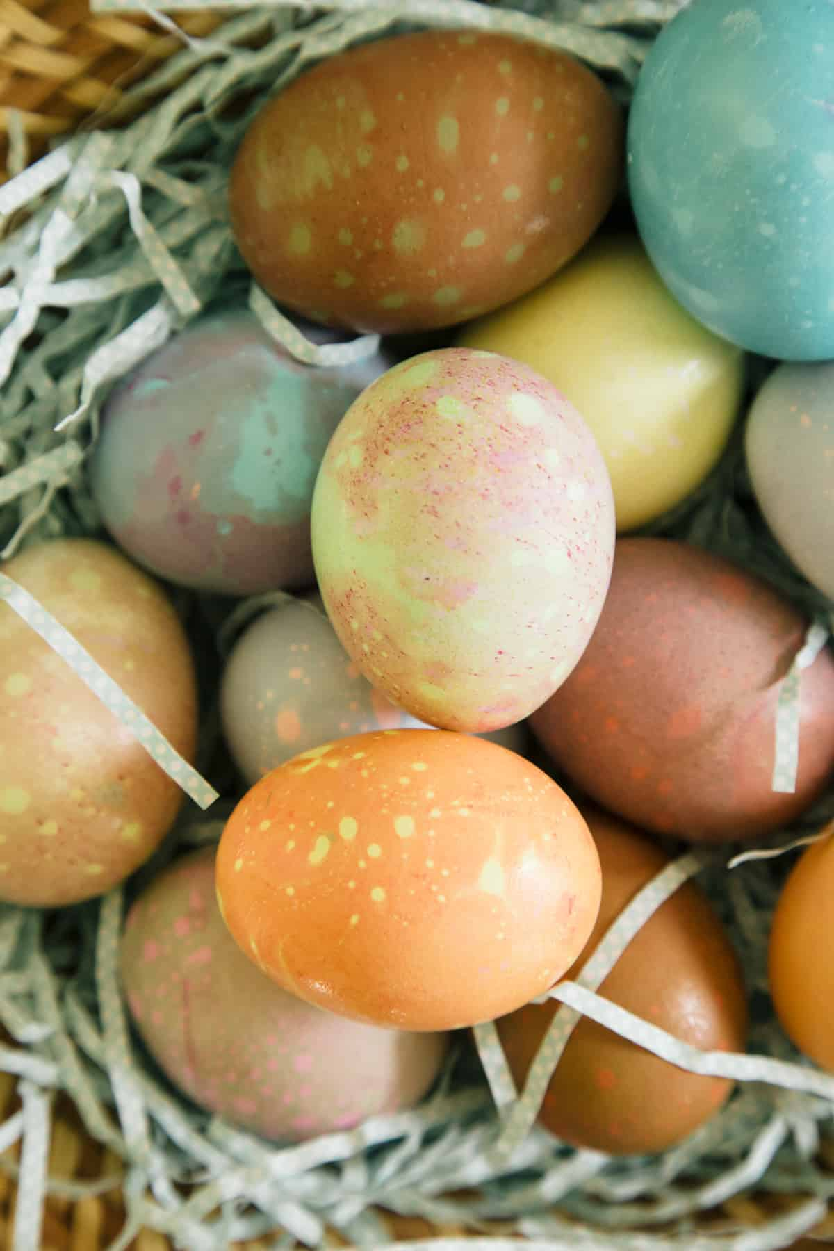 A close up of spotted Easter eggs on Easter grass.