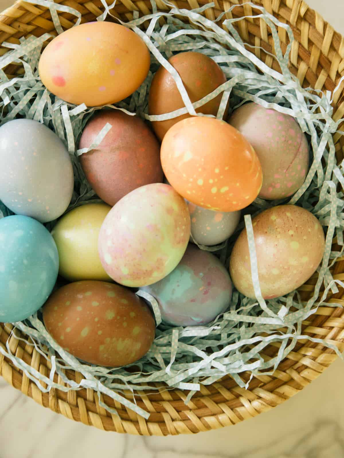 A close up of spotted Easter eggs in a basket.