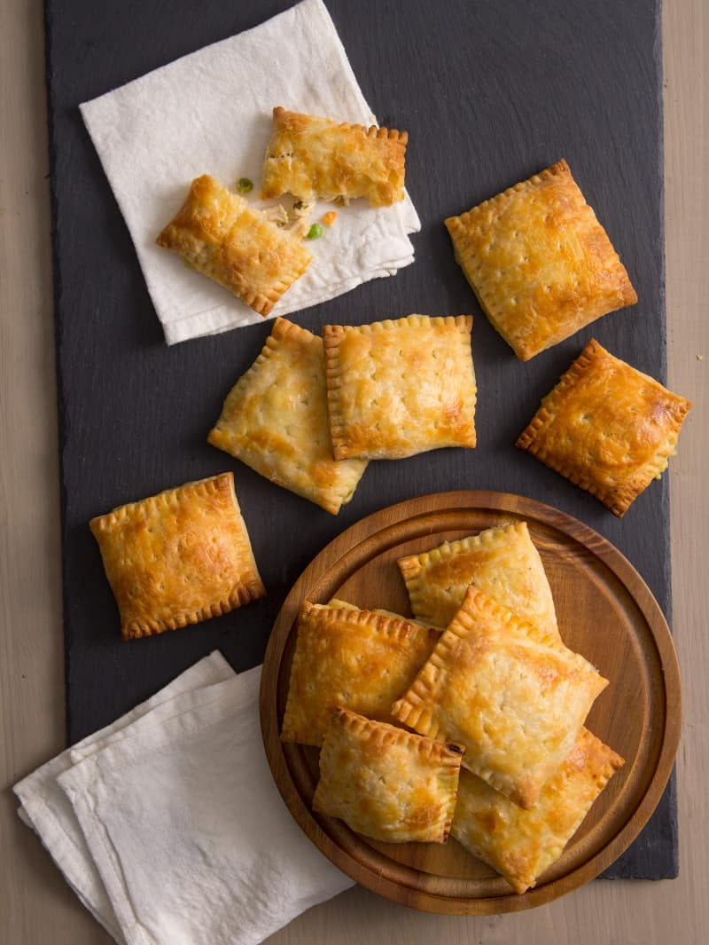 Several chicken pot pie hand pies on a dark board, a round wooden board and napkins.