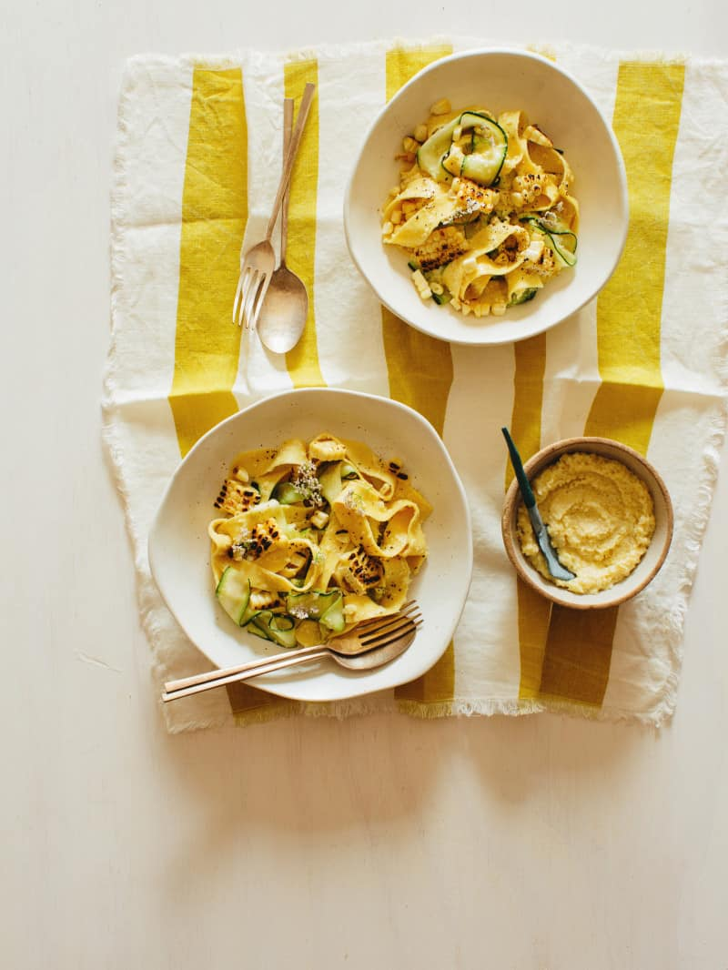Bowls of sweet corn pesto with pappardelle and zucchini noodles on linens with forks and spoons.
