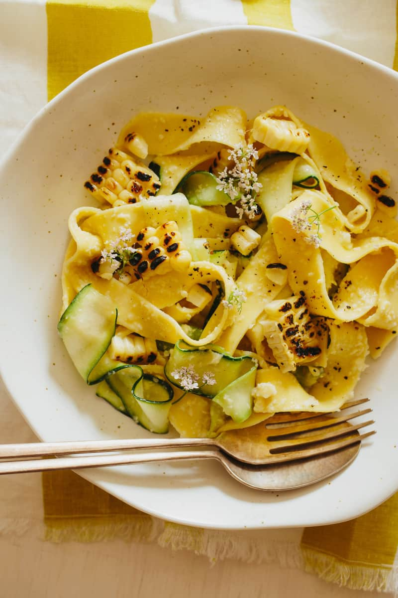 A close up of a bowl of sweet corn pesto with pappardelle and zucchini noodles.