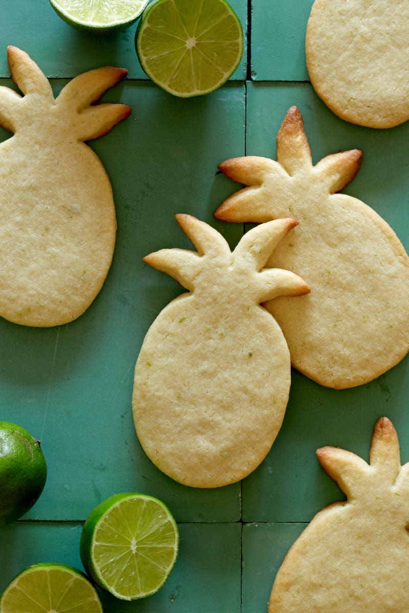 A close up of pineapple shaped lime sugar cookies with limes.