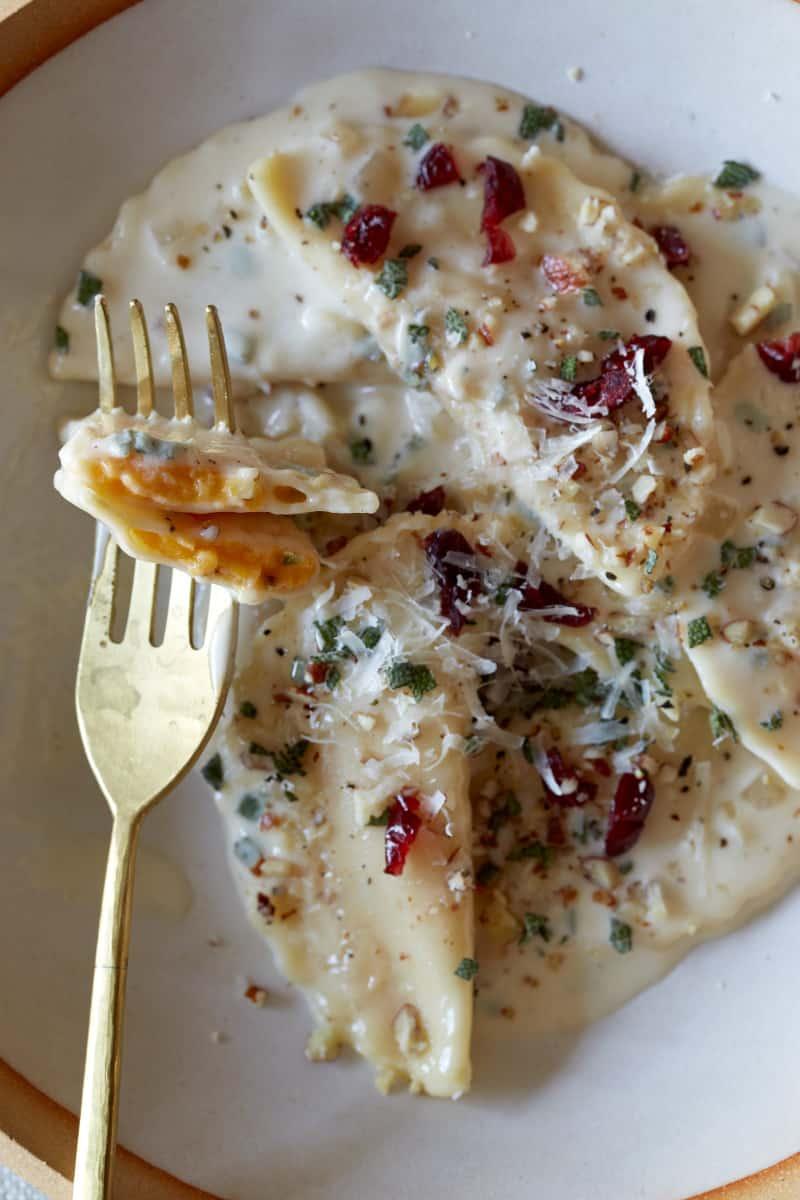 A close up of butternut squash mezzaluna with roasted garlic sage cream sauce on a fork.