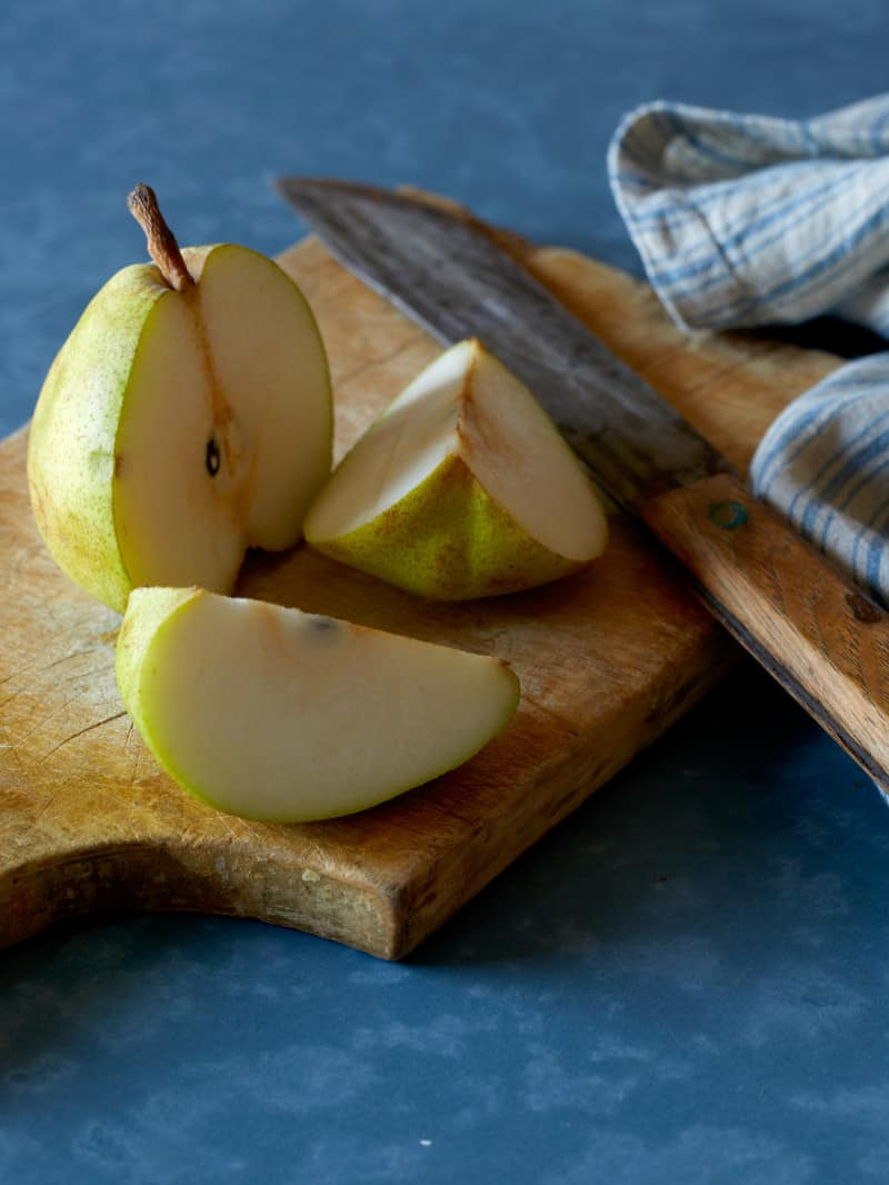 A sliced pear on a wooden cutting board with a tea towel and a knife.