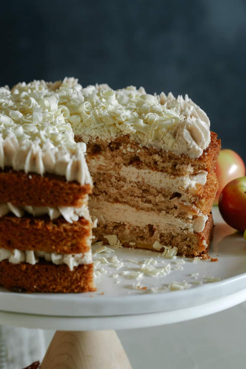 A close up of an apple cake with chai buttercream frosting with visible interior layers.