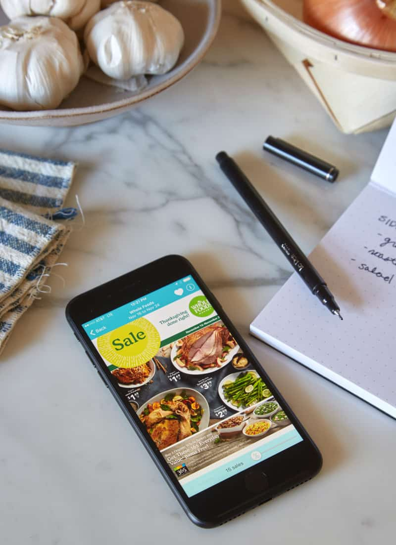 A phone next to a pen and paper list on a marble countertop.