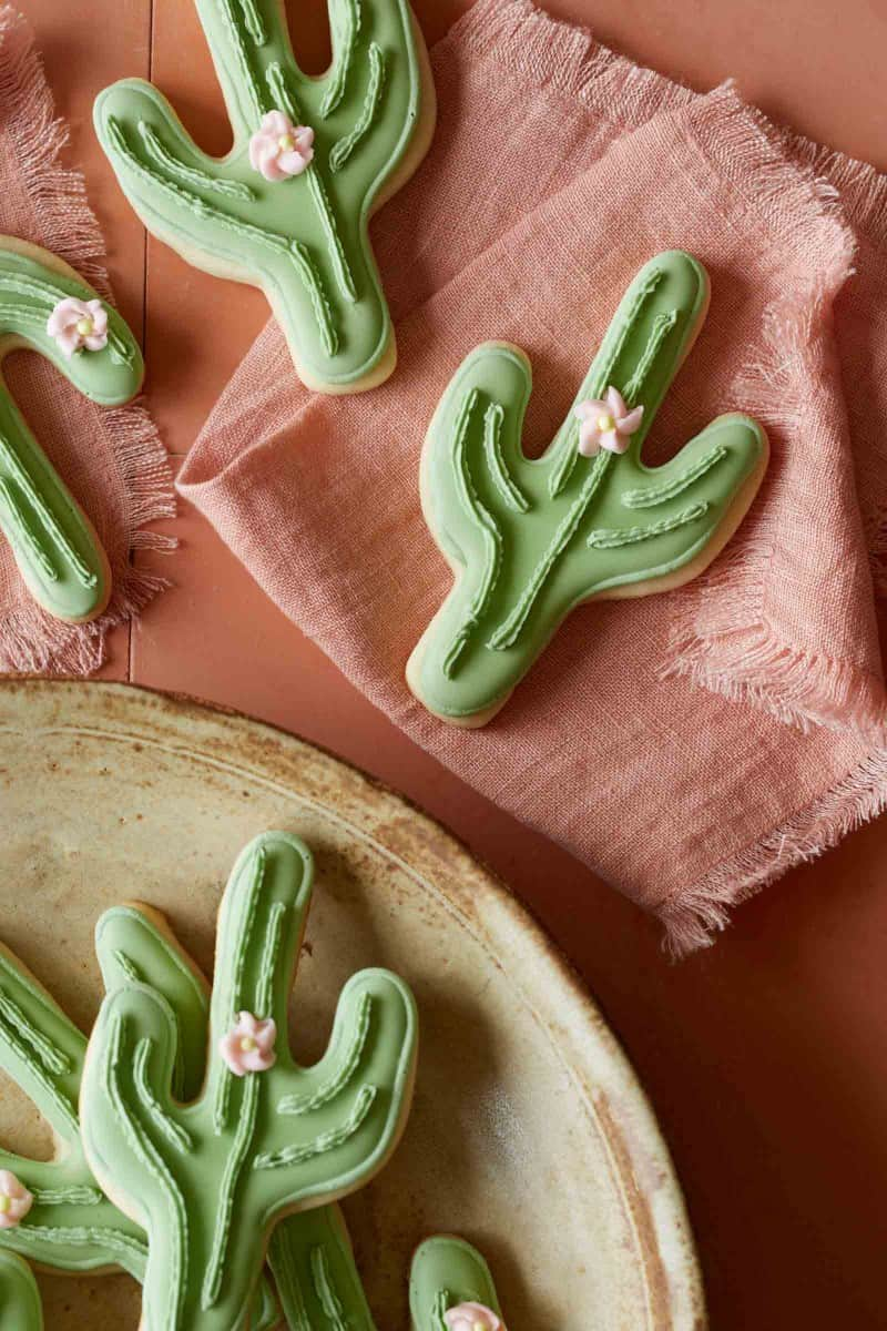 Cactus cookies on a plate and pink linens.