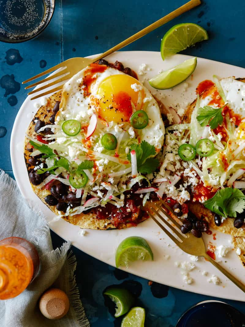 A plate of huevos rancheros with black beans and chipotle salsa with forks.
