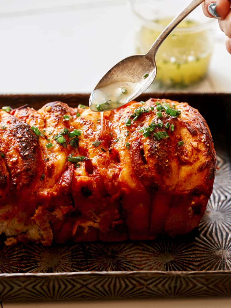 Pizza pull apart bread with a spoon drizzling garlic herb butter on top.