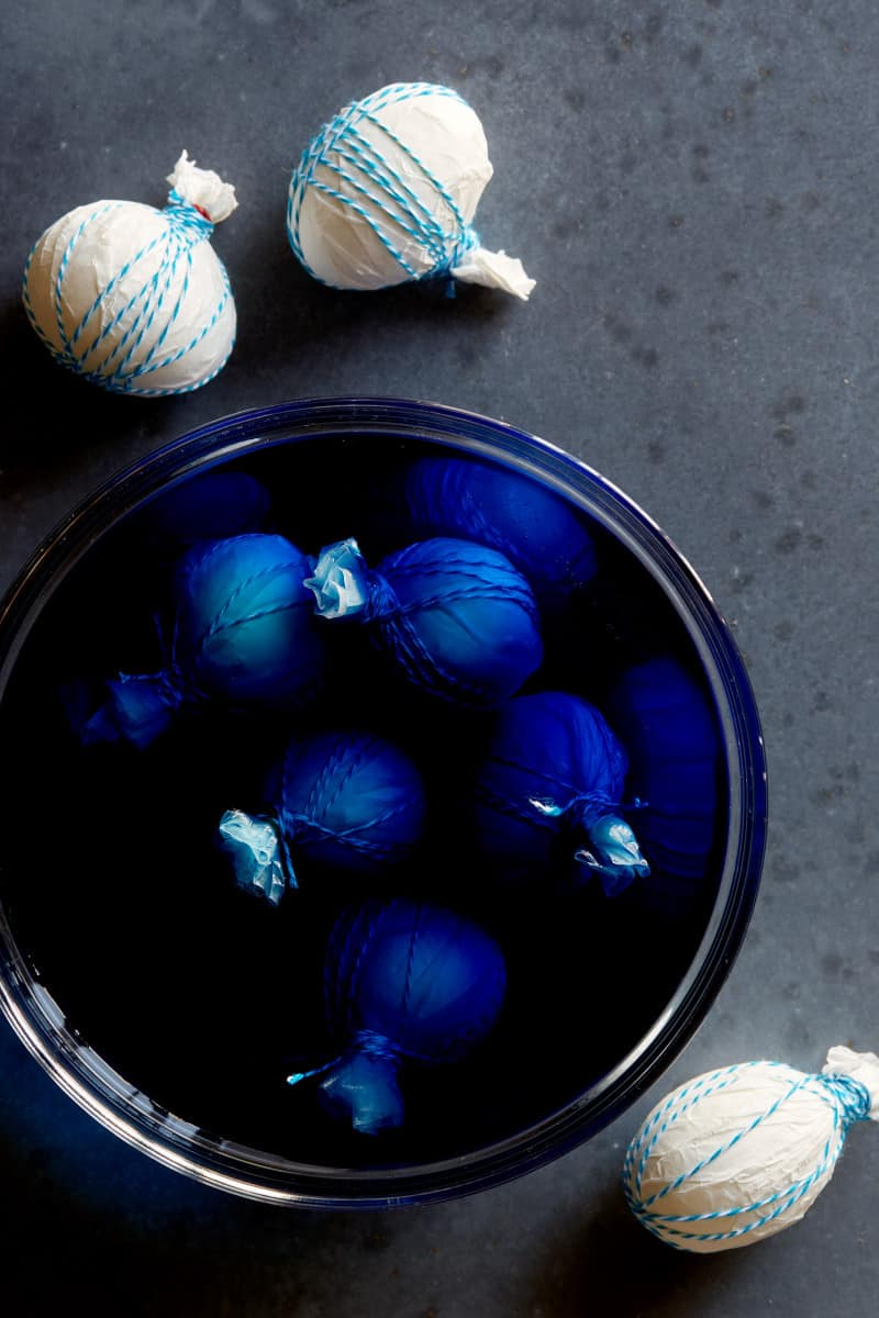 DIY shibori style easter eggs before and after being dyed blue.