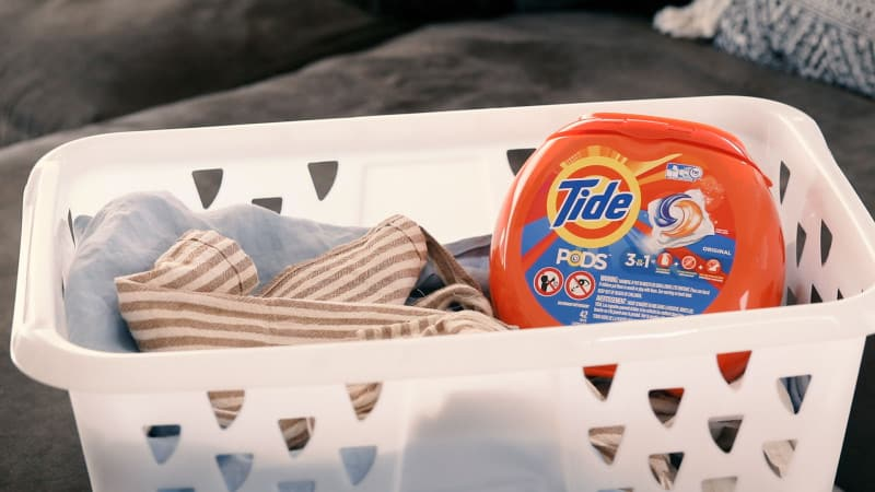 Tide pods in a laundry basket with linens.