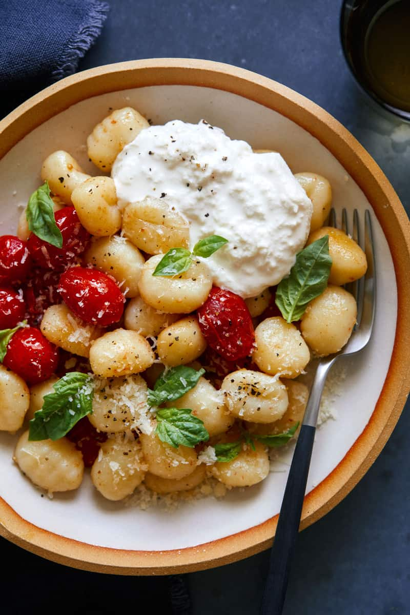 A close up of a bowl of caprese gnocchi and a fork.