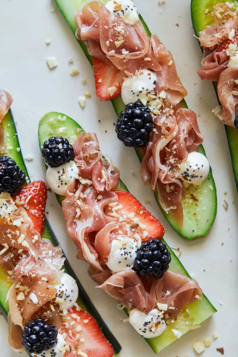 A close up of a plate of prosciutto cucumber crostini.