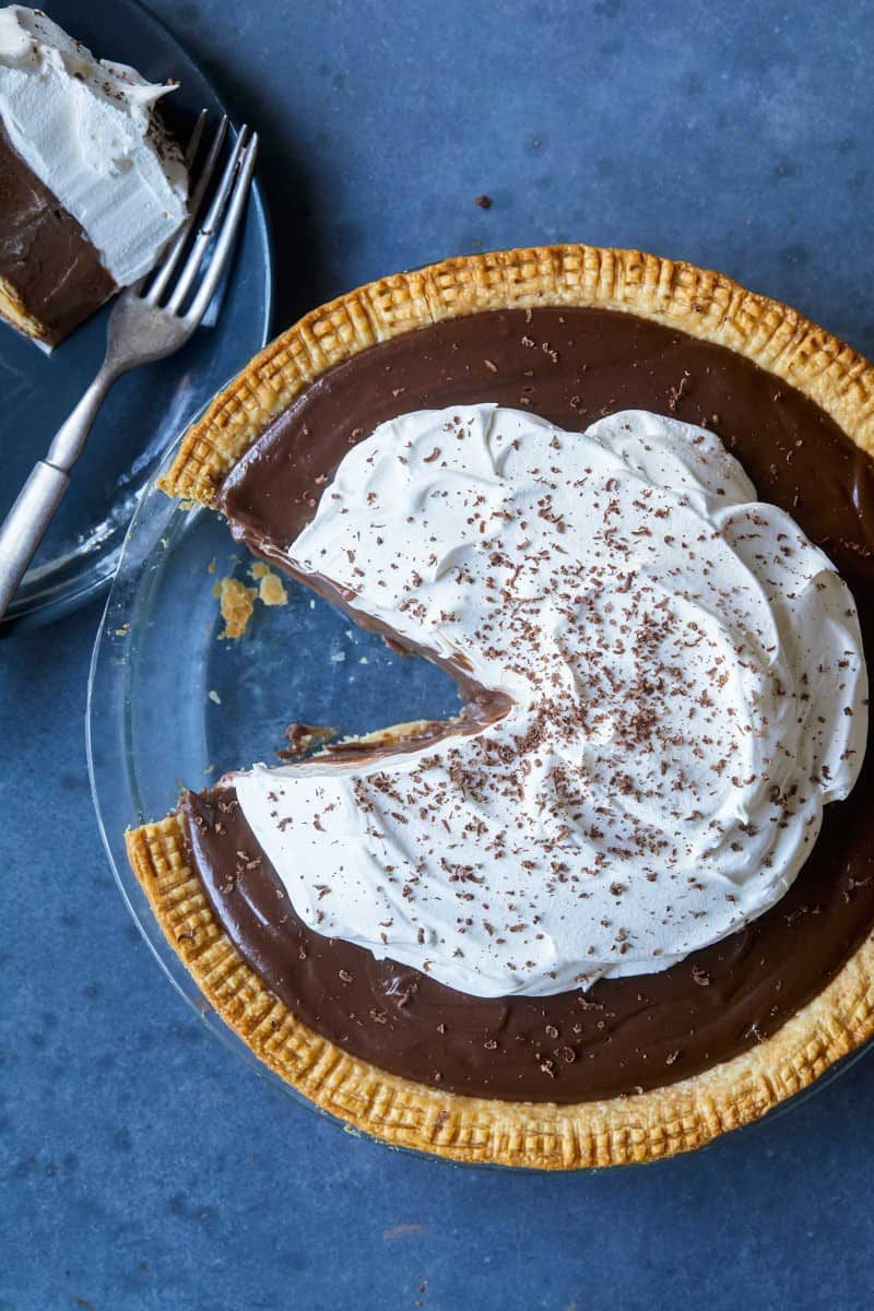 A whole chocolate cream pie with a slice taken out and served with a fork.