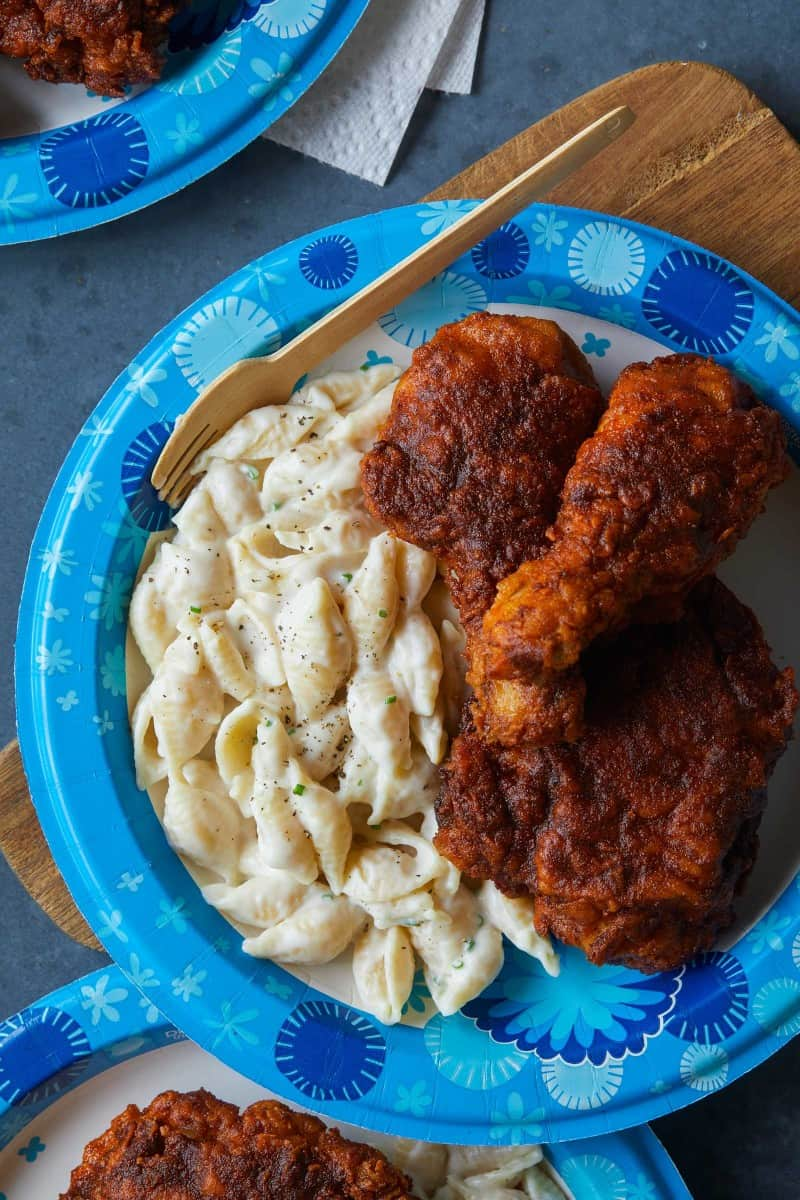 A close up of a Dixie paper plates of Nashville hot chicken with mac and cheese.