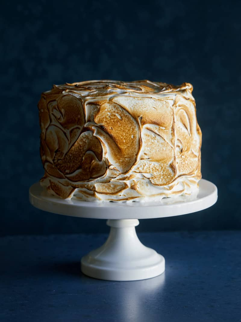 A six layer s\'mores cake on a white cake stand.