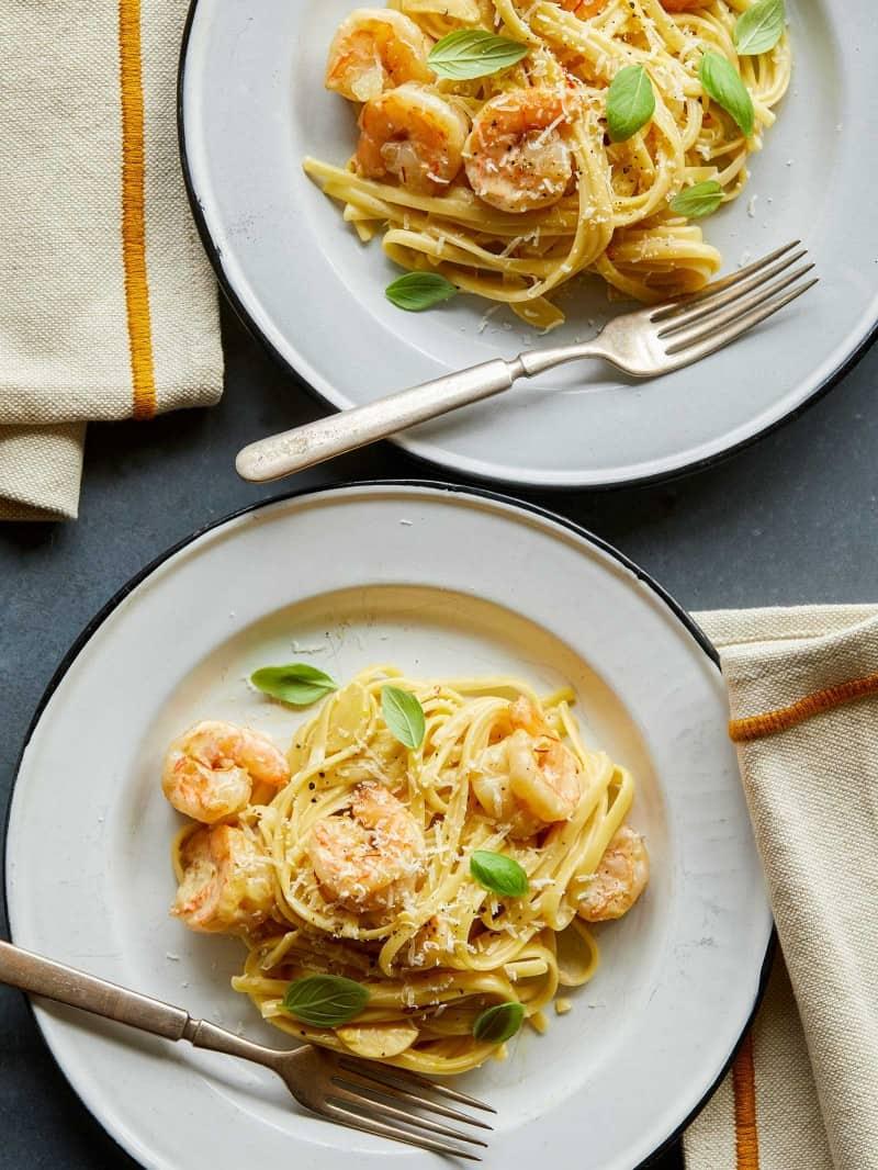 A plates of shrimp linguine and garlic and saffron cream sauce with forks.