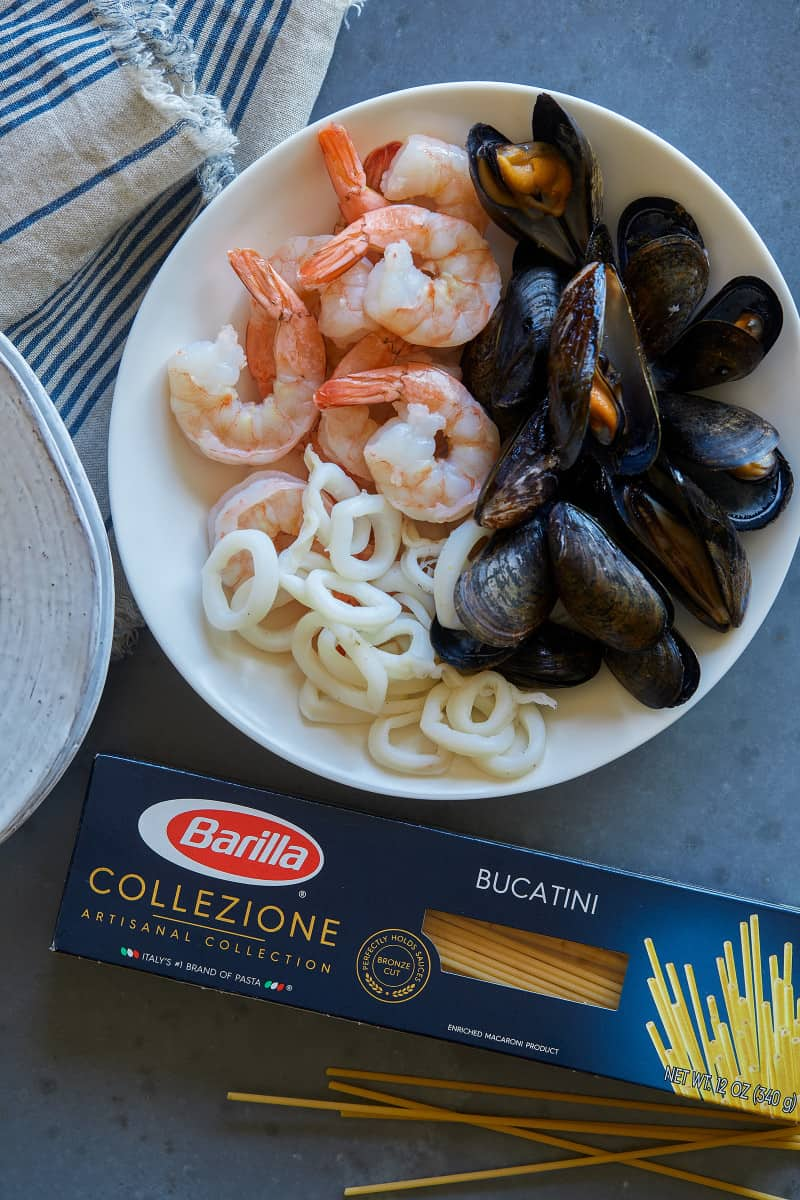 Ingredients for seafood carbonara in a bowl next to a box of Barilla Collezione Bucatini.