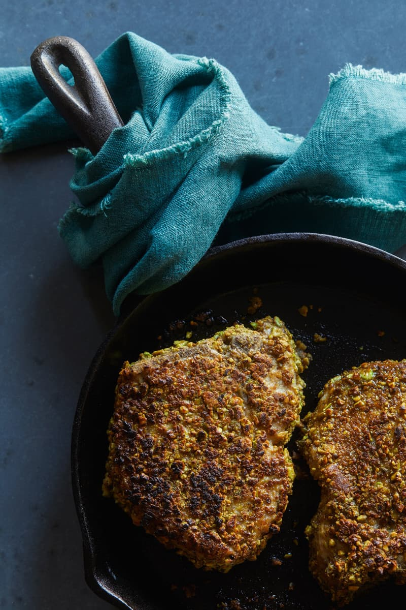 Pistachio crusted pork chop in a skillet.