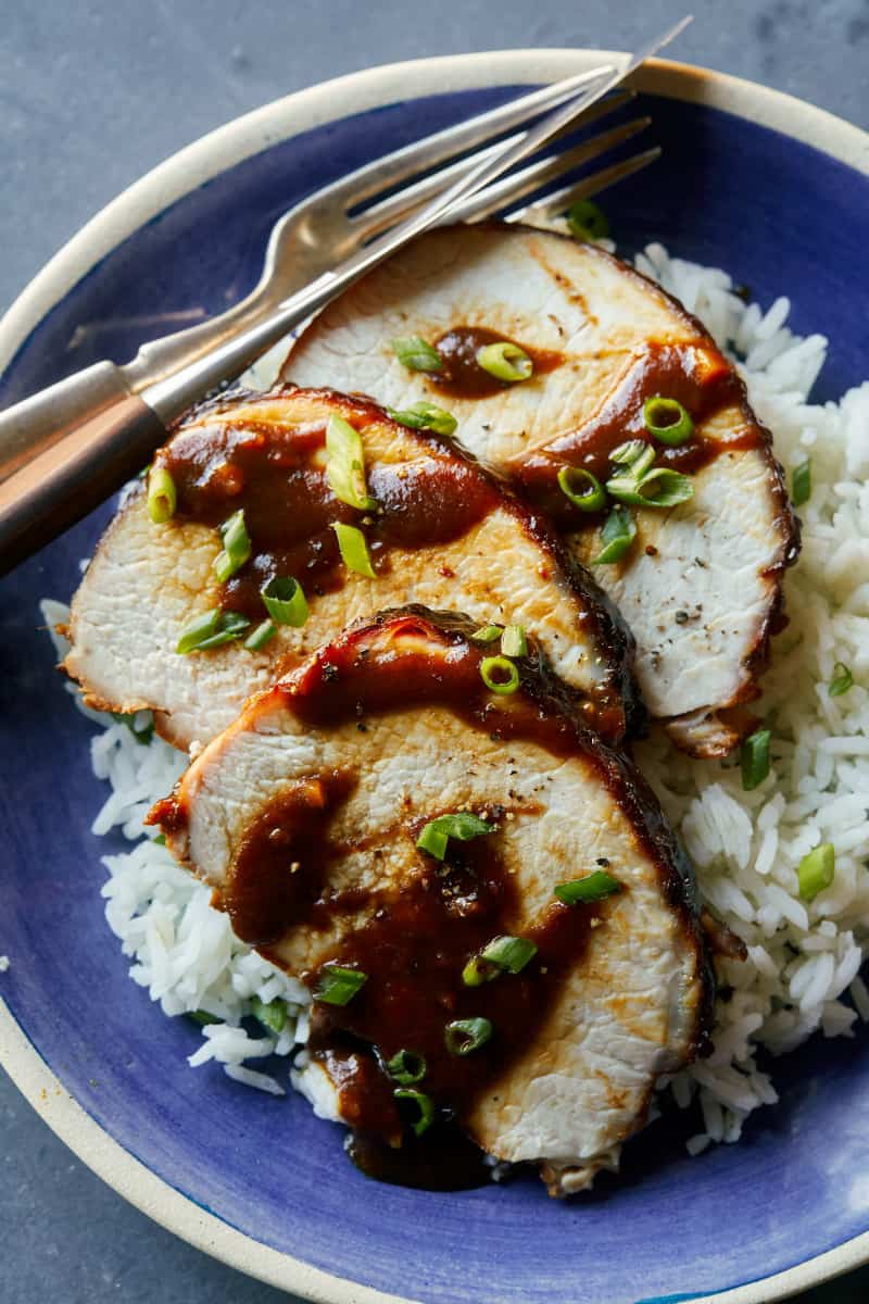 A plate of sliced char siu pork tenderloin over white rice and a fork and knife.