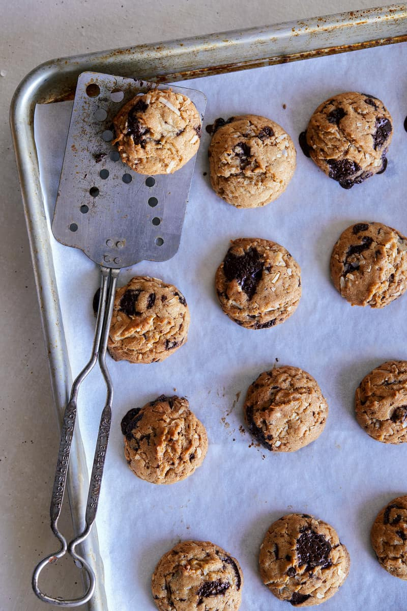 Baked chai, chocolate chip, and coconut cookies on a baking sheet with a spatula.