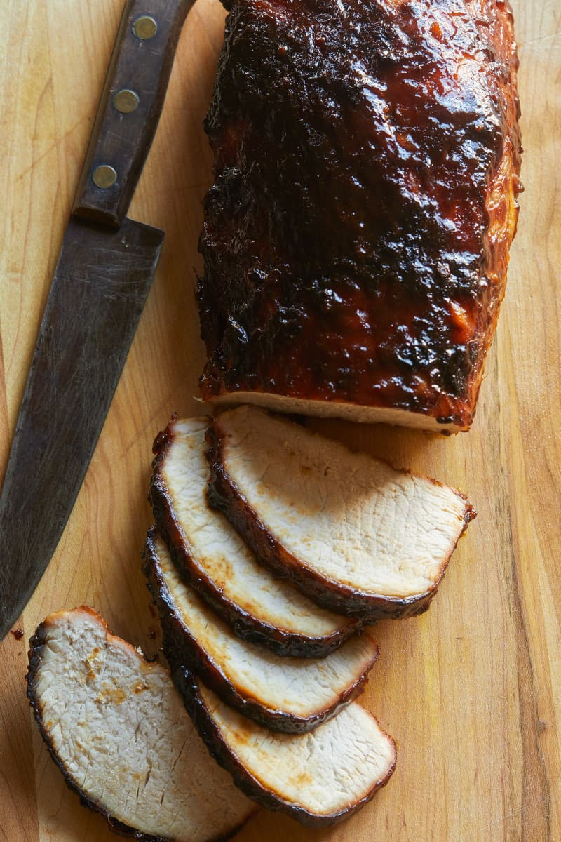 Char siu pork tenderloin, half sliced on a wooden cutting board with a knife.