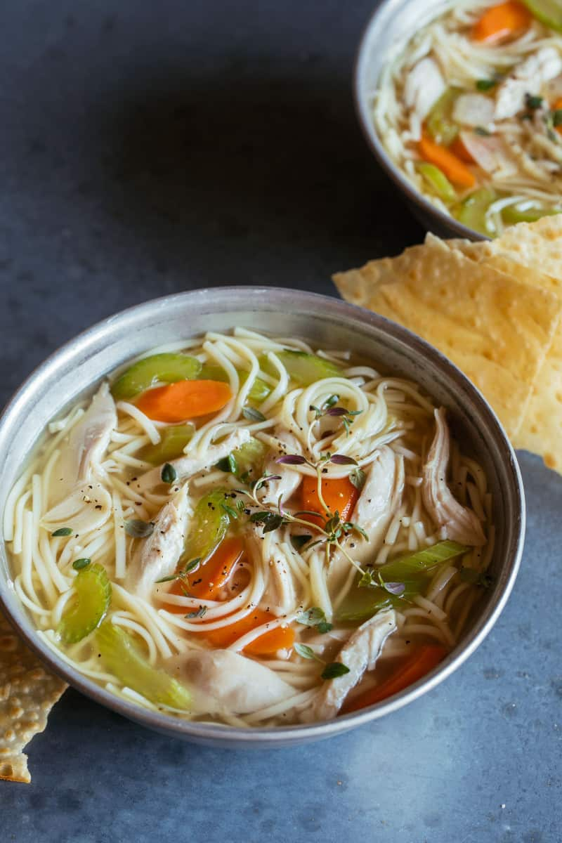 Bowls of chicken noodle soup with crackers.