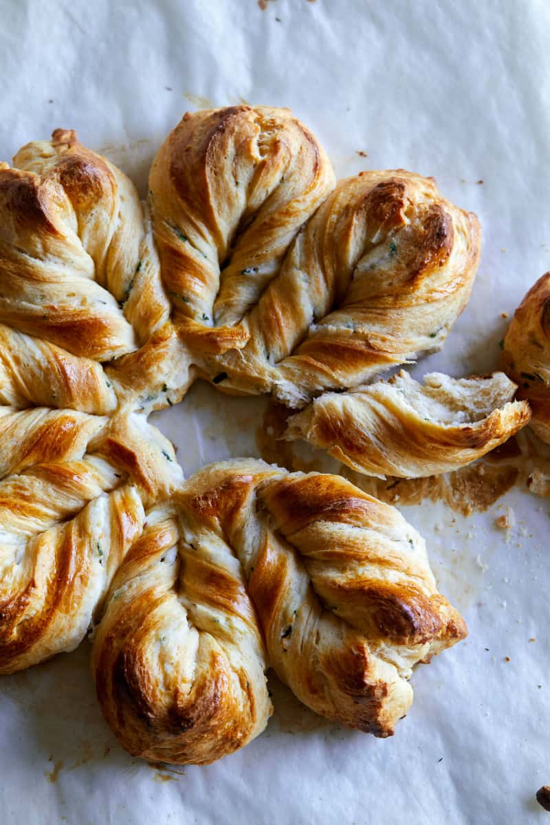 A close up of herb and cheese braided star bread with some pulled off.