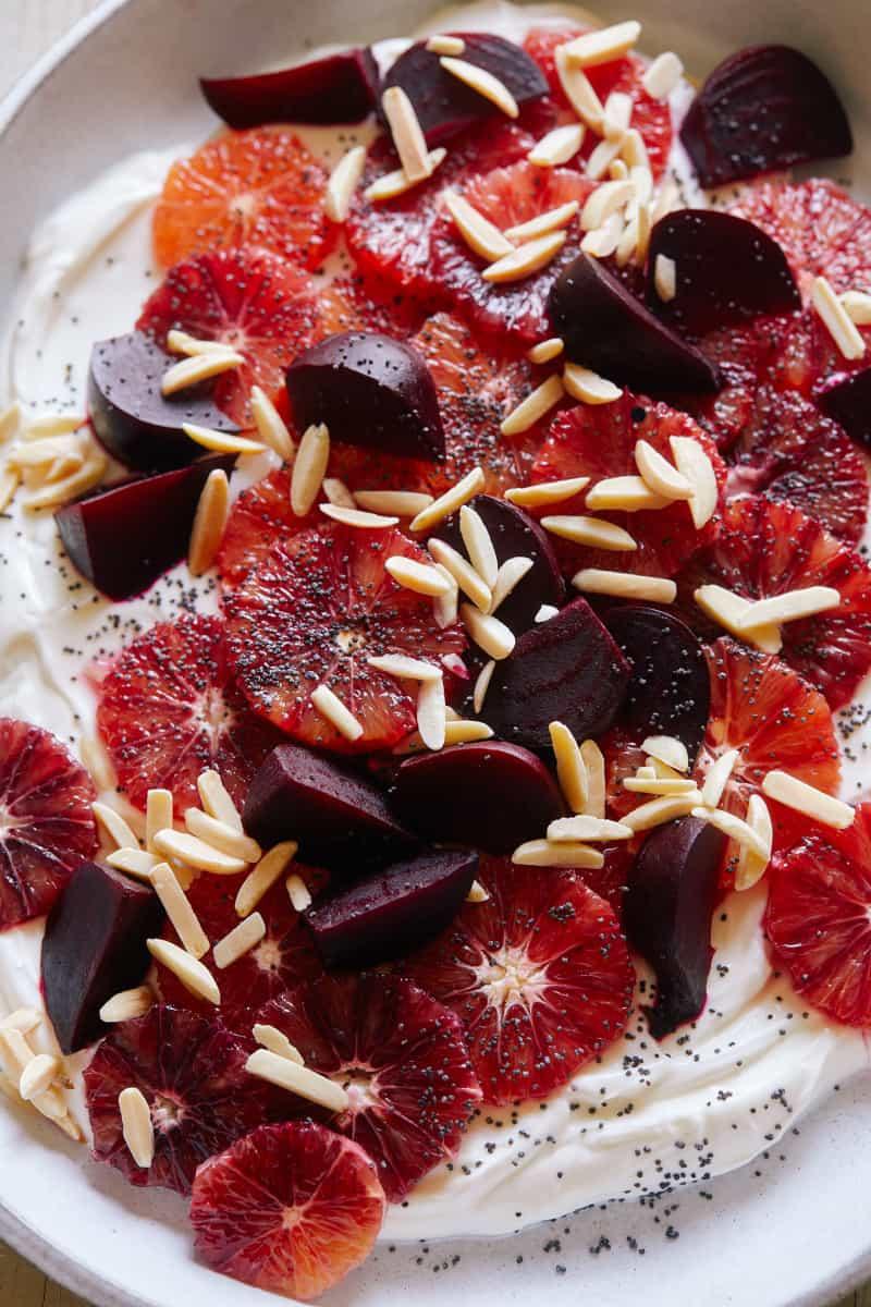 A close up of blood orange and beet salad over honeyed yogurt.