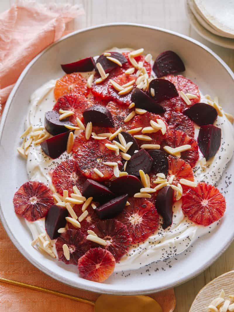 Blood orange and beet salad over honeyed yogurt in a bowl.