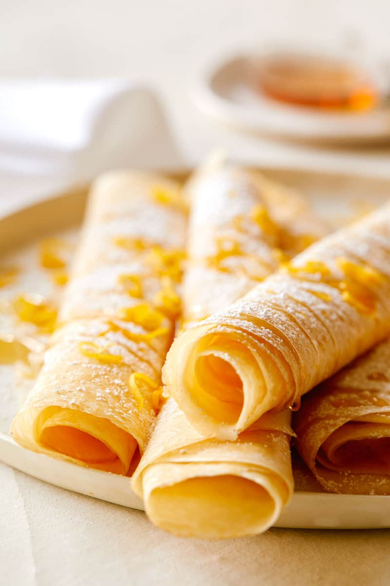 A close up of meyer lemon and ricotta stuffed crepes on a plate.