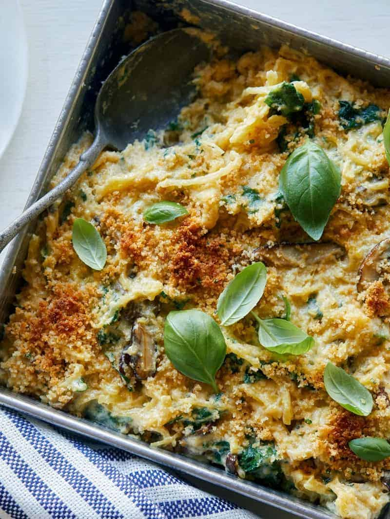 A close up of creamy vegan spaghetti squash, wild mushroom, and spinach bake with a spoon.